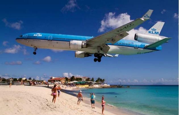 Los aviones aterrizan a muy poca distancia de los turistas.Los turistas tienen como atractivo y diversión resistir a las ráfagas del avión